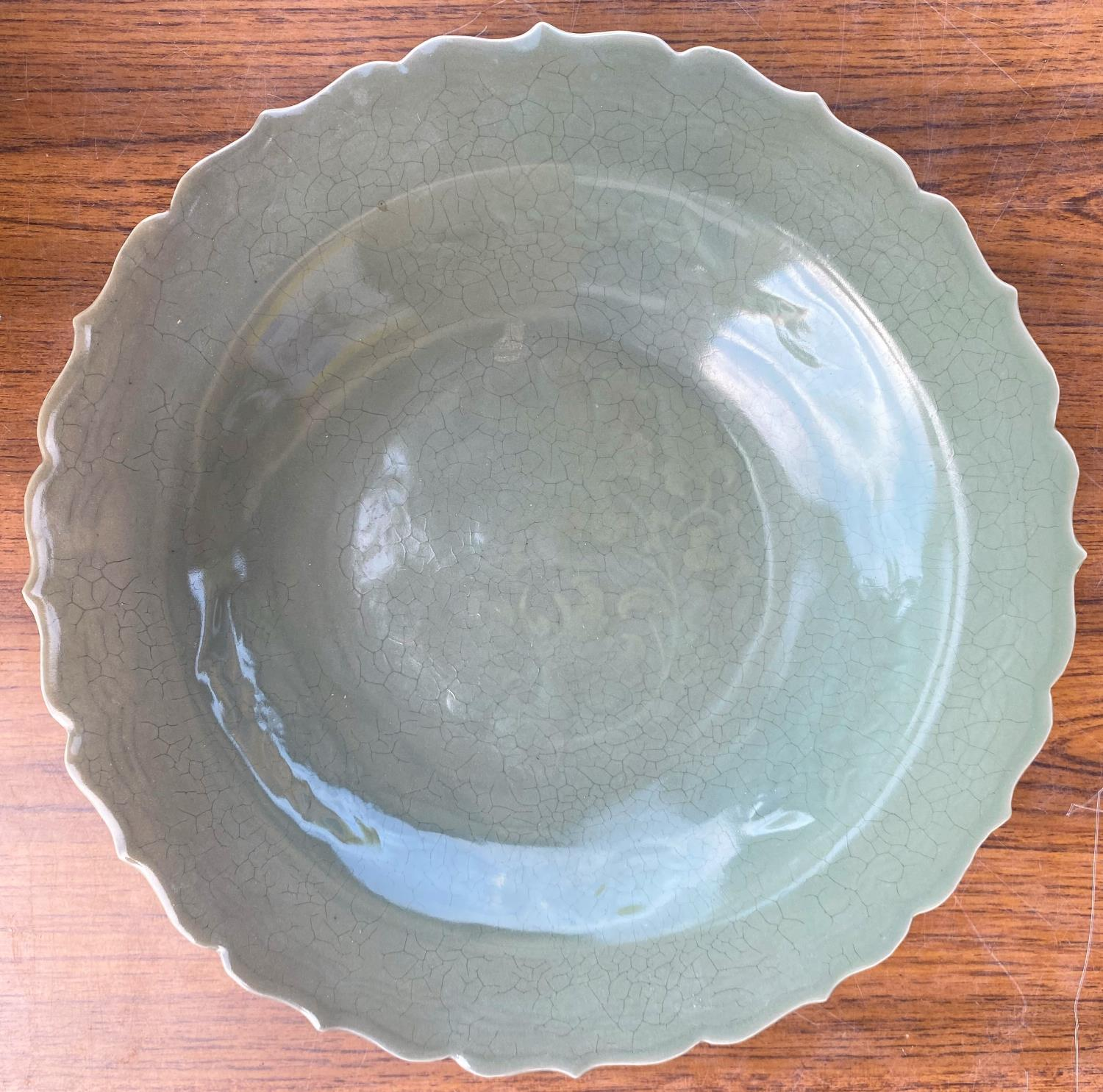 A Chinese celadon glaze dish with scalloped border, diameter 31cm and a carved Chinese hardwood