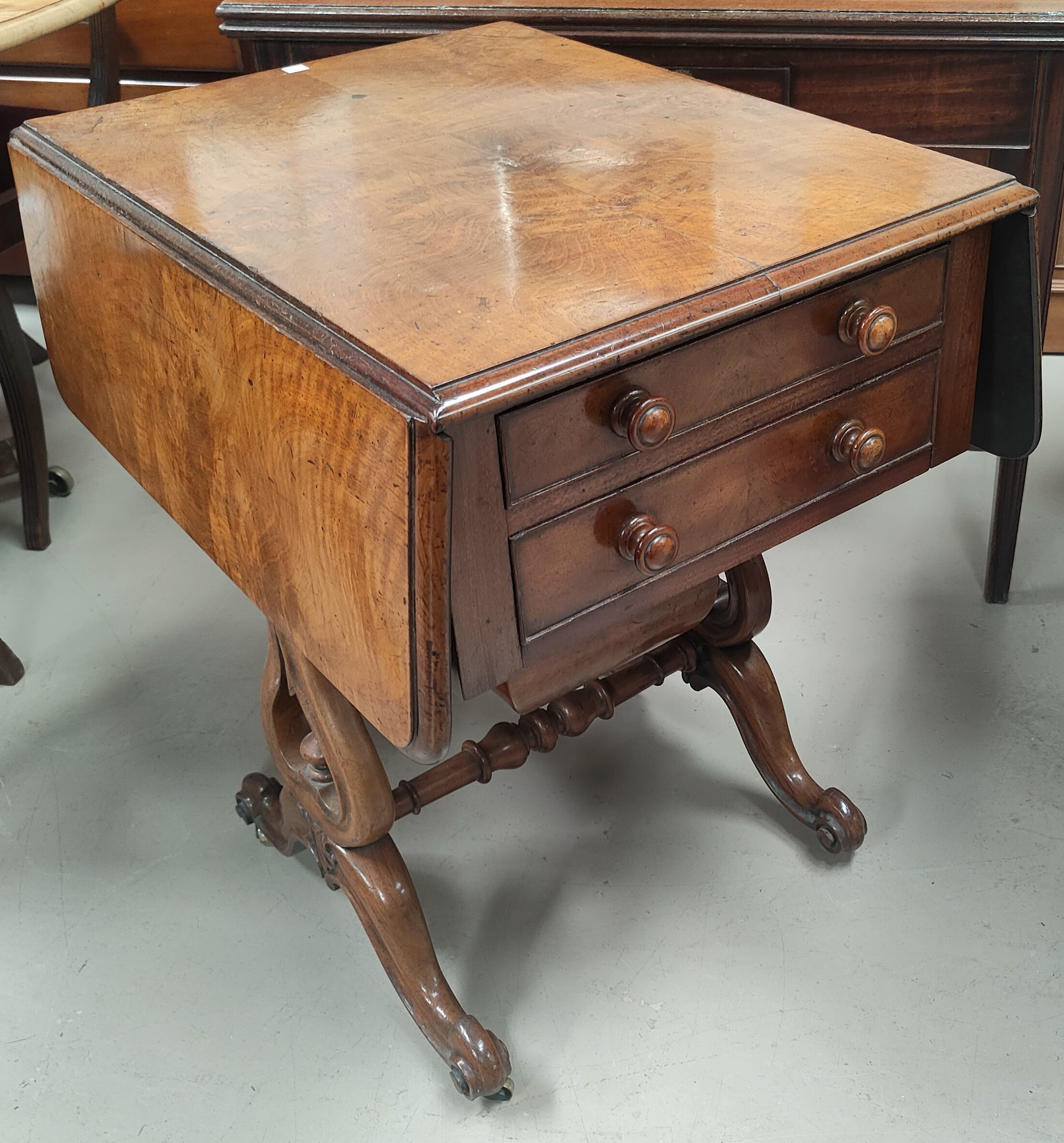 A Victorian walnut Pembroke/work table with two frieze drawers and sliding well on lyre supports,