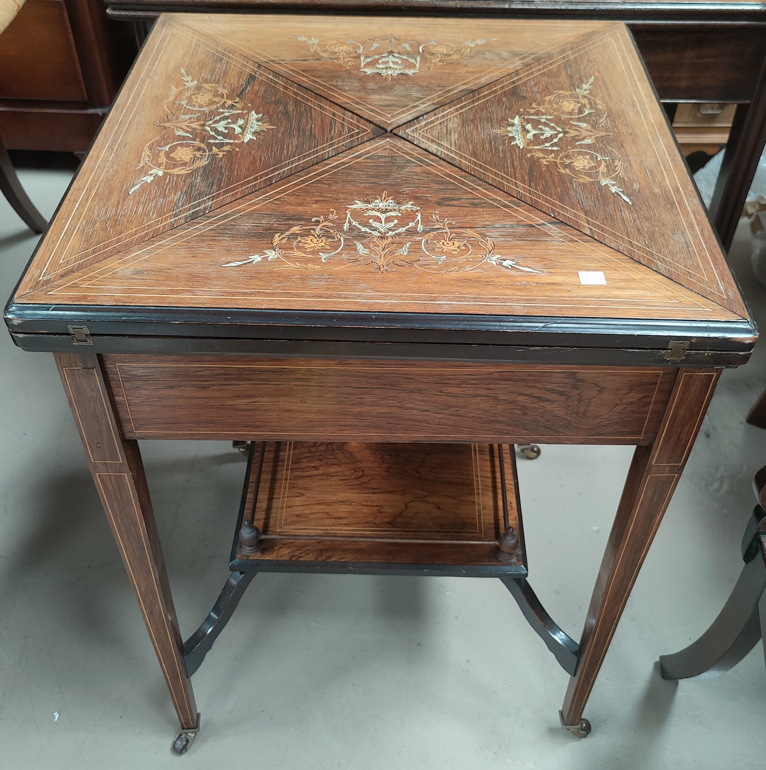 A Victorian Rosewood envelope card table with floral inlay to the top with satinwood inlay with