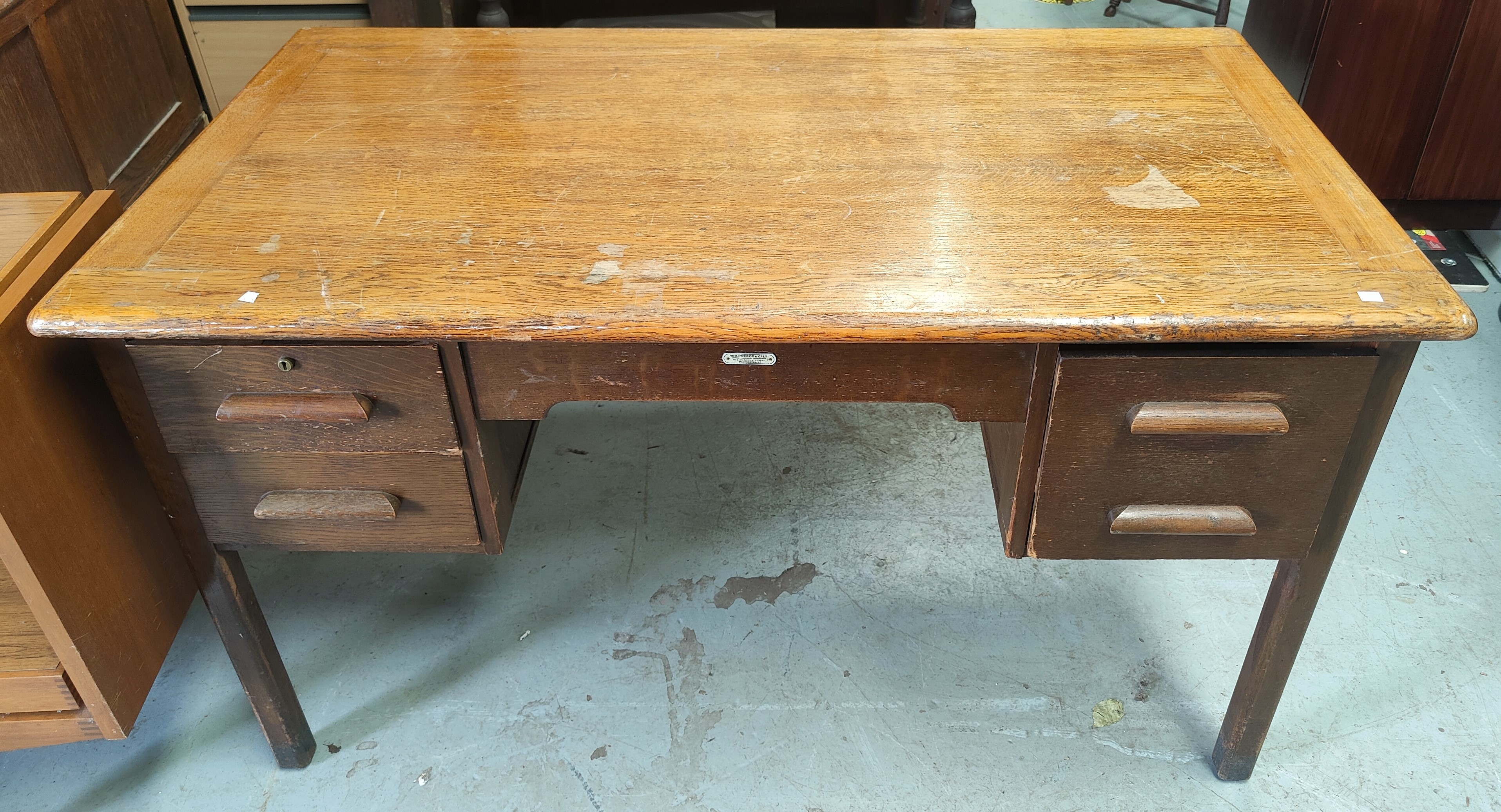 A large vintage oak W.H.Priest and Sons teachers desk with rectangular rounded top, three drawers on