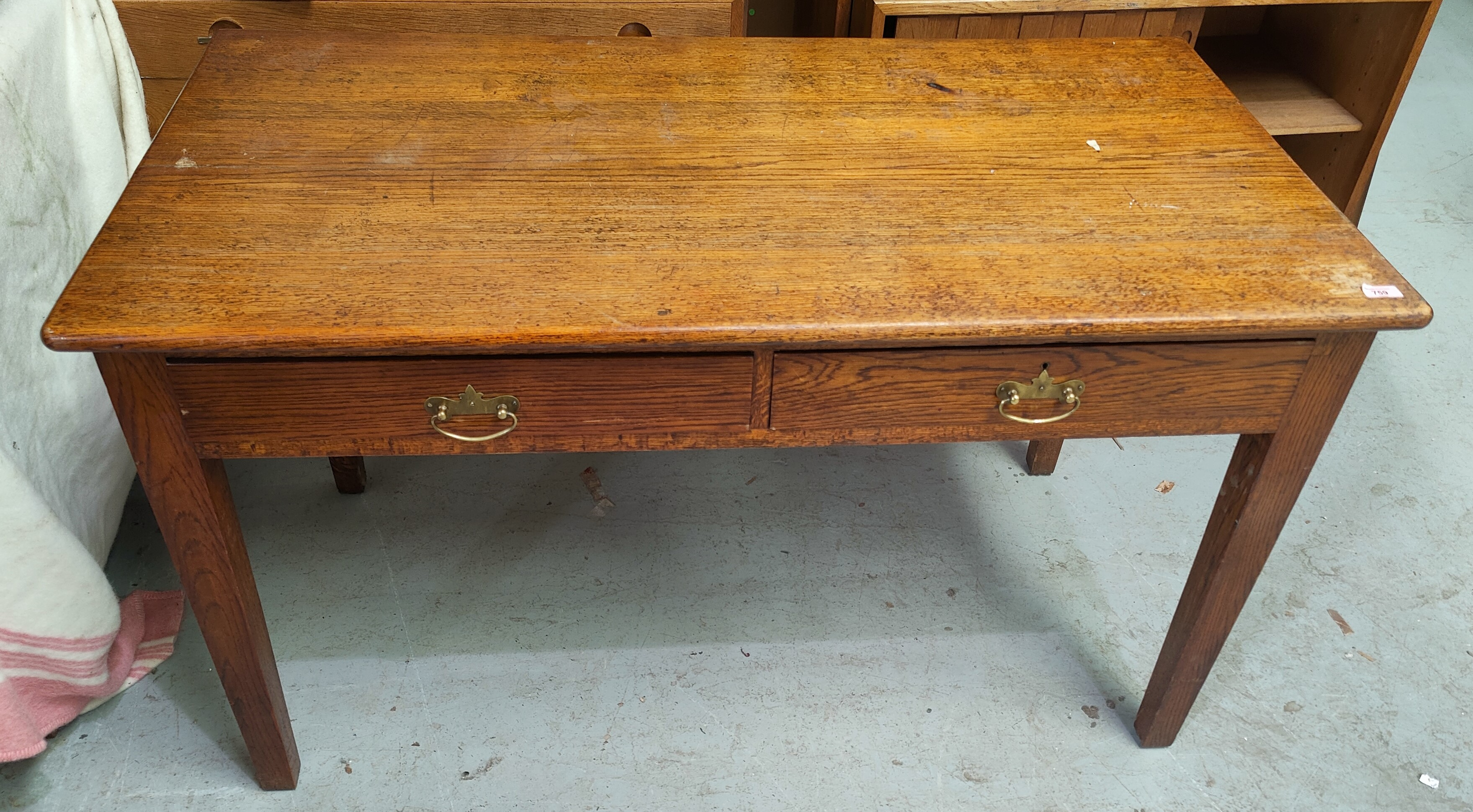 An early 20th century oak desk, possibly military, with crown G.R.V. stamped under, with two