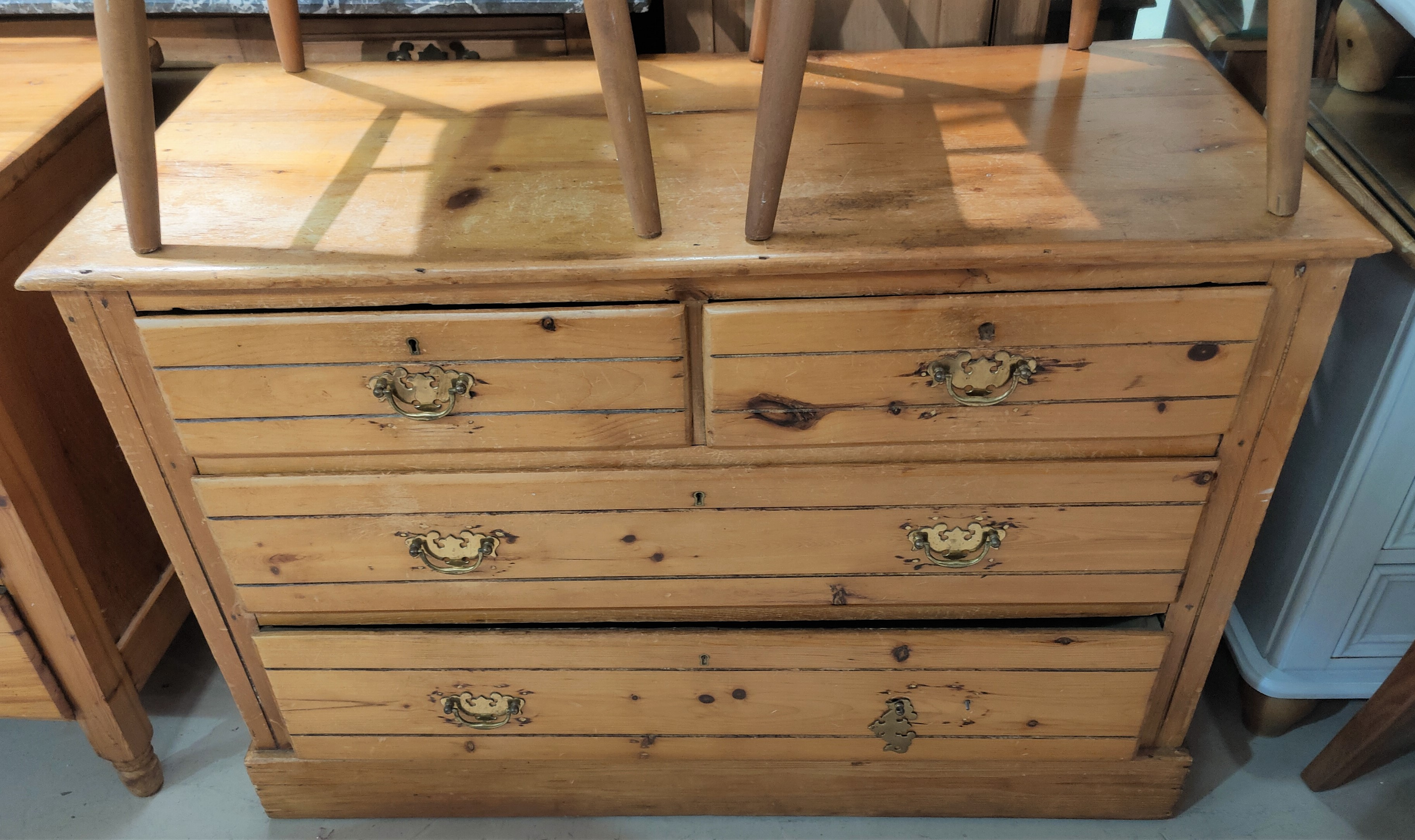 An Edwardian stripped pine chest of 2 long and 2 short drawers