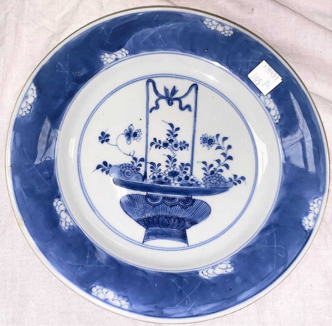 An 18th century Chinese blue and white plate with central panel featuring floral arrangement, wide