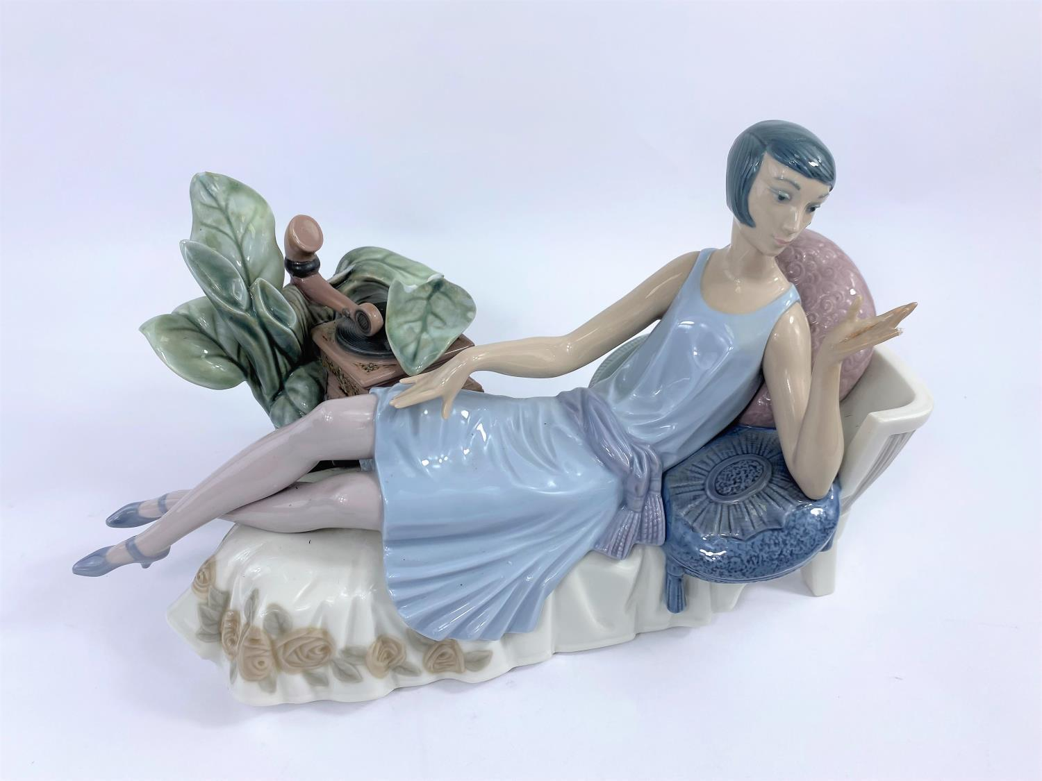 A Lladro group: 1920's girl on chaise longue with gramophone (a.f.)