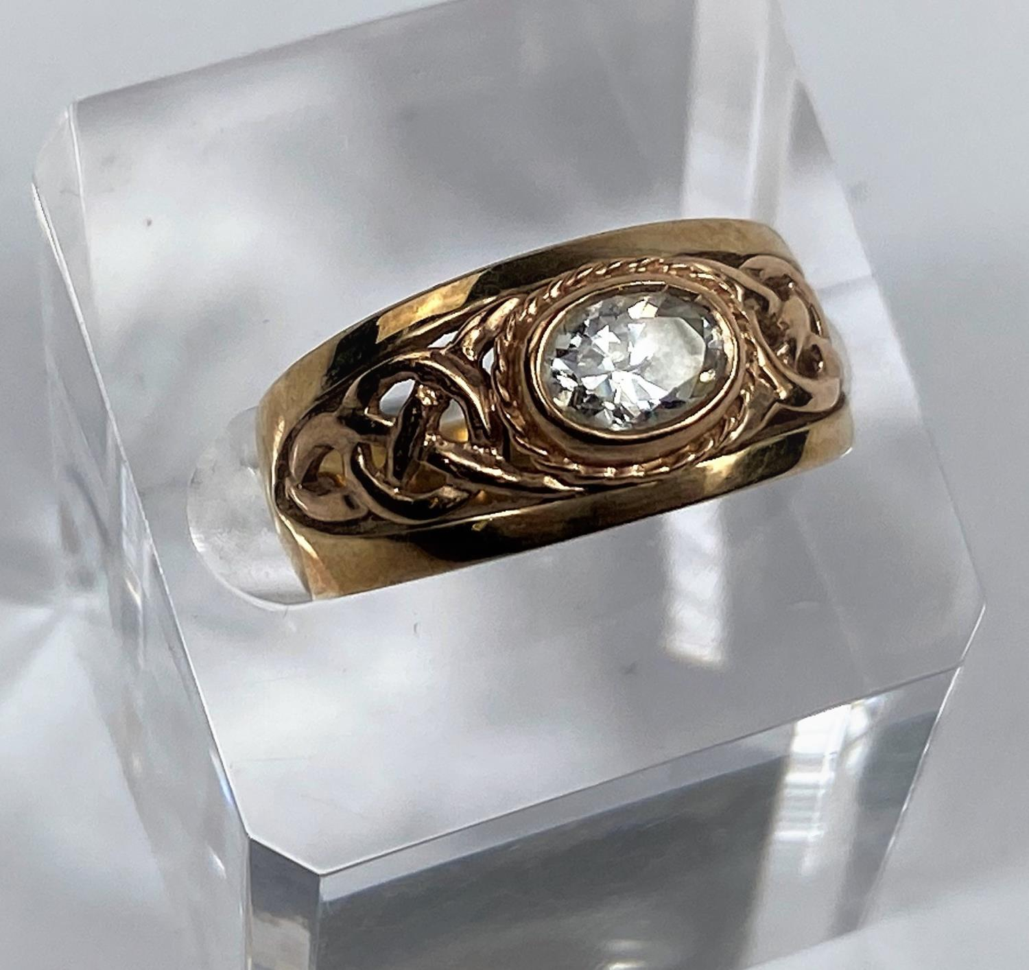 A 9 carat hallmarked gold period style ring set clear oval stone, the split shank with pierced