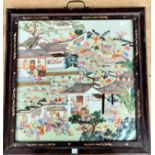 A large Chinese ceramic tile with polychrome decoration of a busy festival scene with musicians,