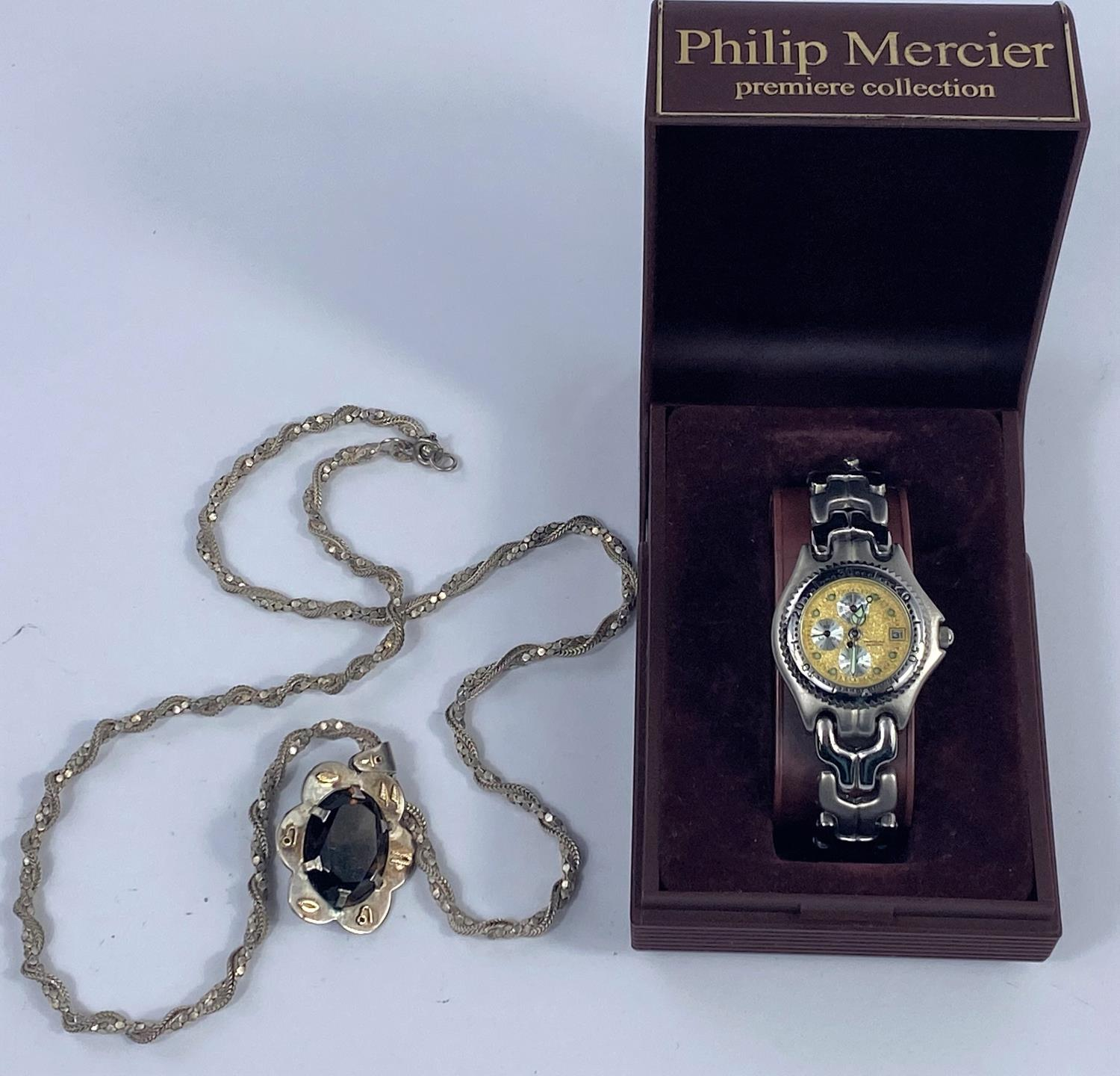 A lady's stainless steel wristwatch with a gilt face & 3 secondary dials; a smoky quarts pendant