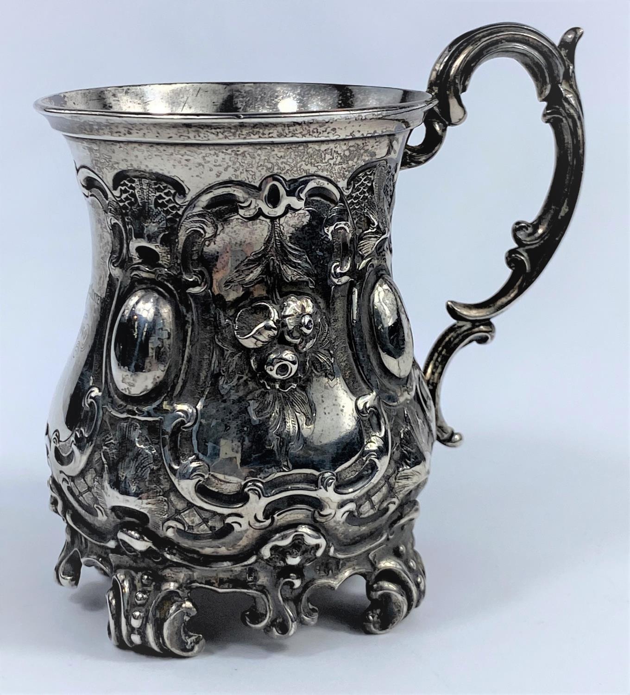 A hallmarked silver Victorian half pint mug on scroll feet, ornate decoration, inscribed, London