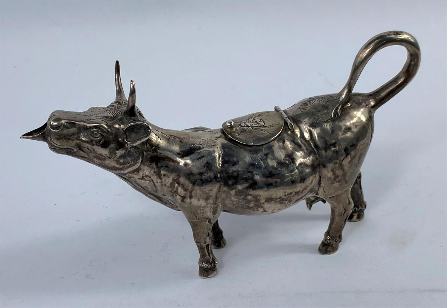 A continental white metal cow creamer with relief chased decoration, the top filling aperture hinged