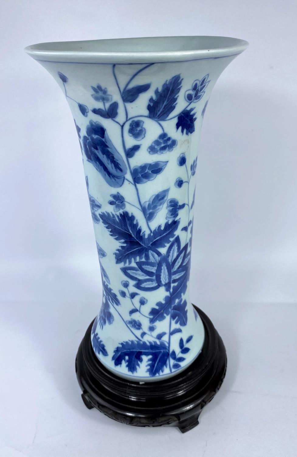 A Chinese porcelain vase of waisted cylindrical form, decorated with flowers and leaves in