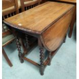 A 1930's oak dining table with oval drop leaf top on barley twist gate legs