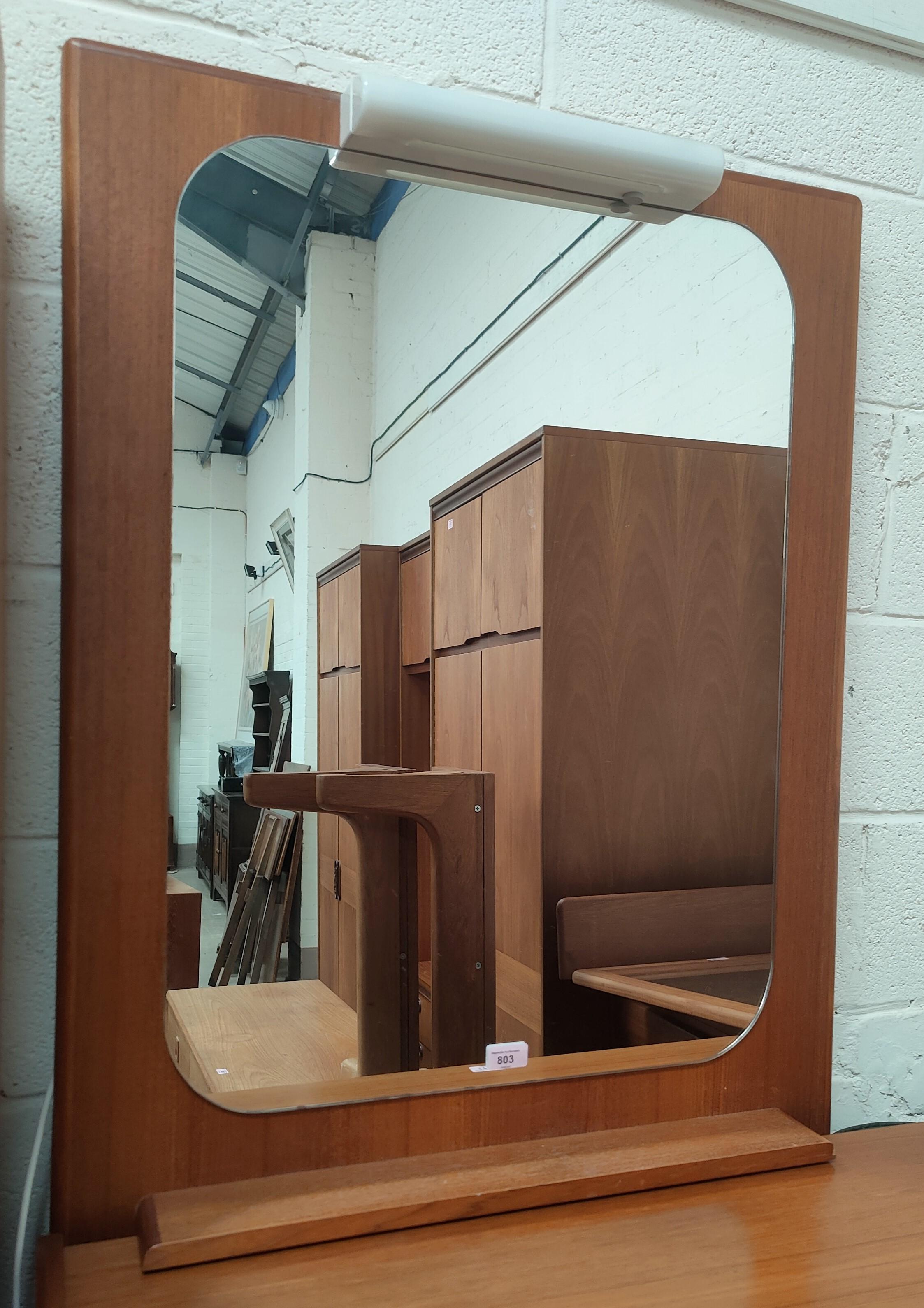 A mid century teak backed mirror with under-shelf
