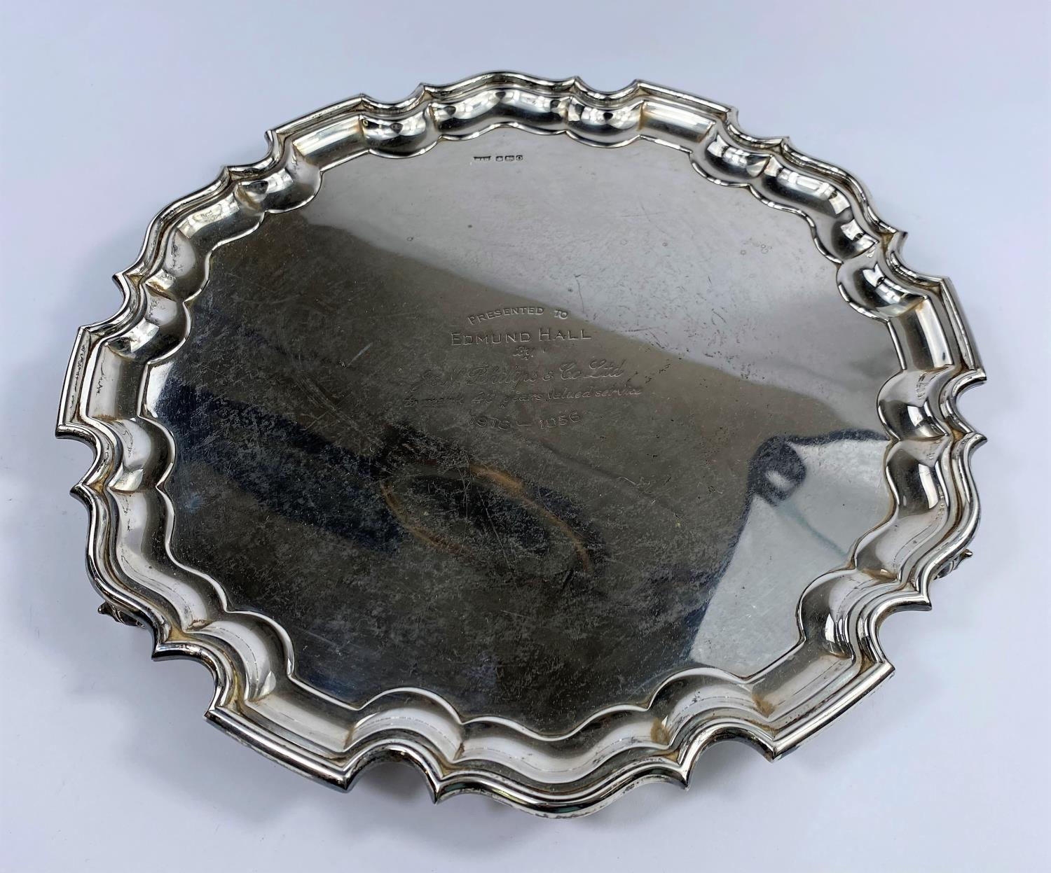 A hallmarked silver circular salver with scalloped edge, on 4 scroll feet, inscribed, Sheffield