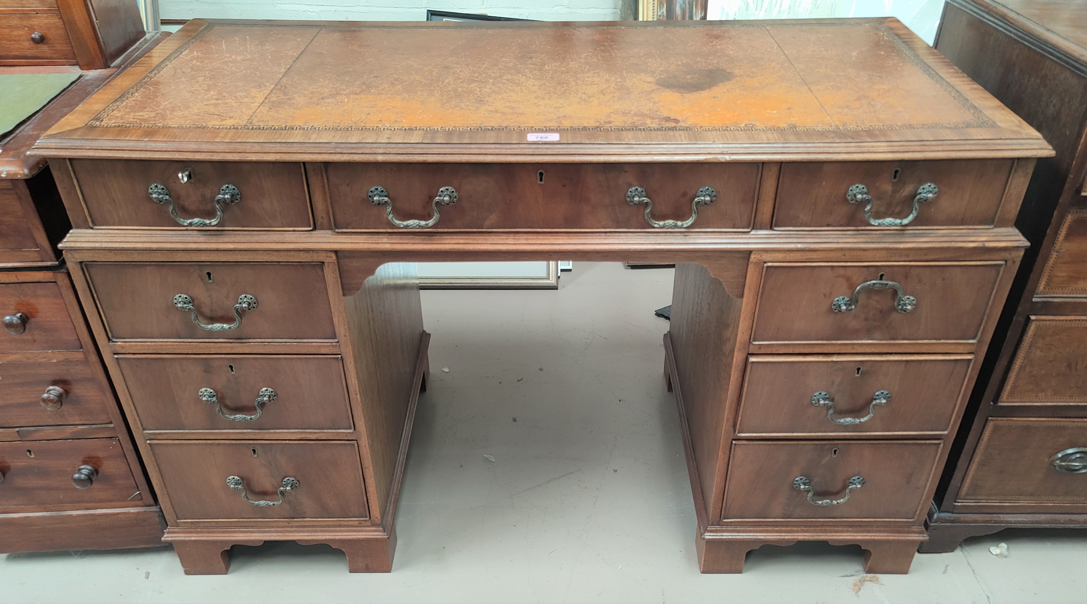 A reproduction mahogany kneehole desk with inset leather top, 3 frieze and 6 pedestal drawers, width