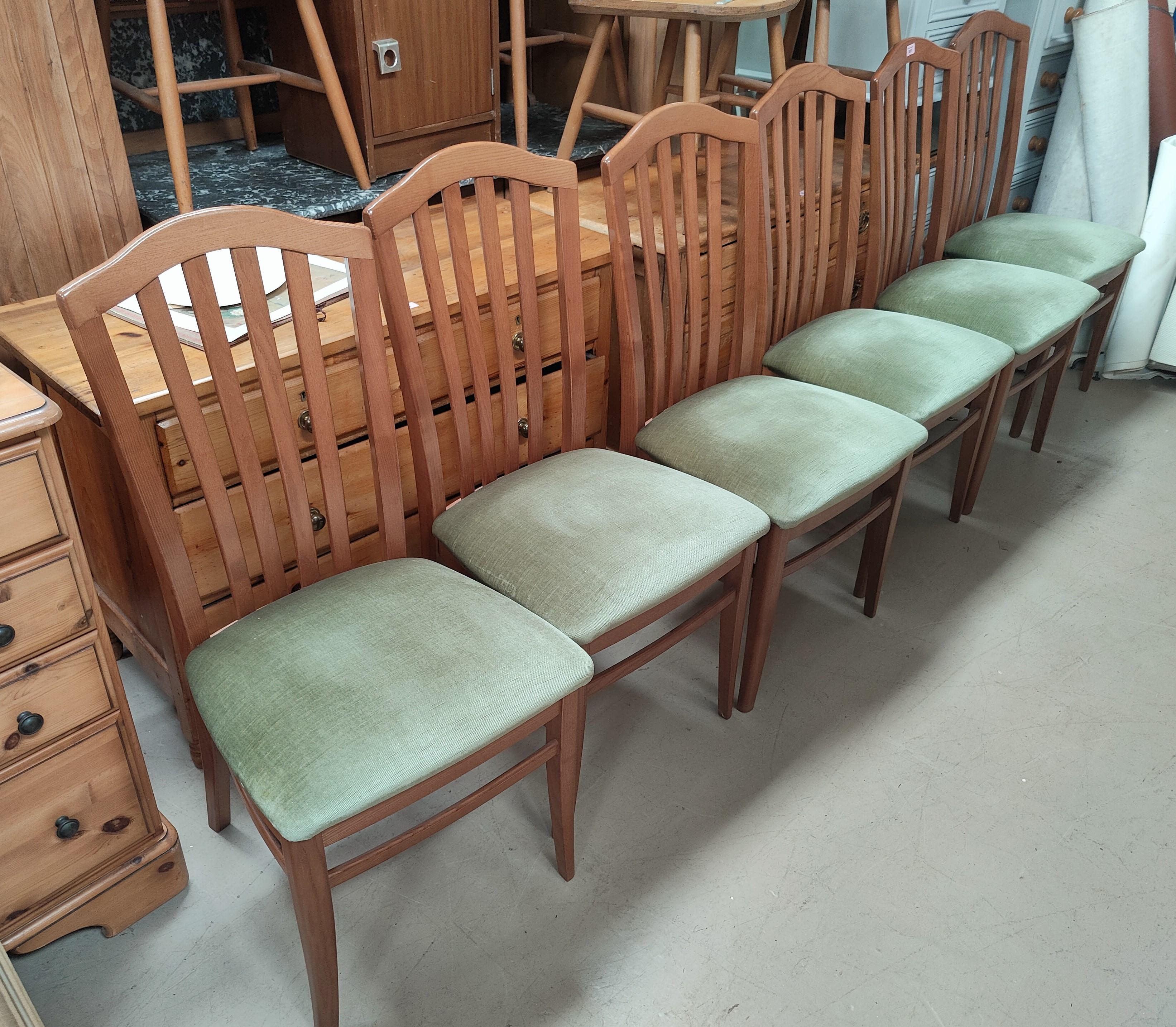 A set of six teak rail back dining chairs