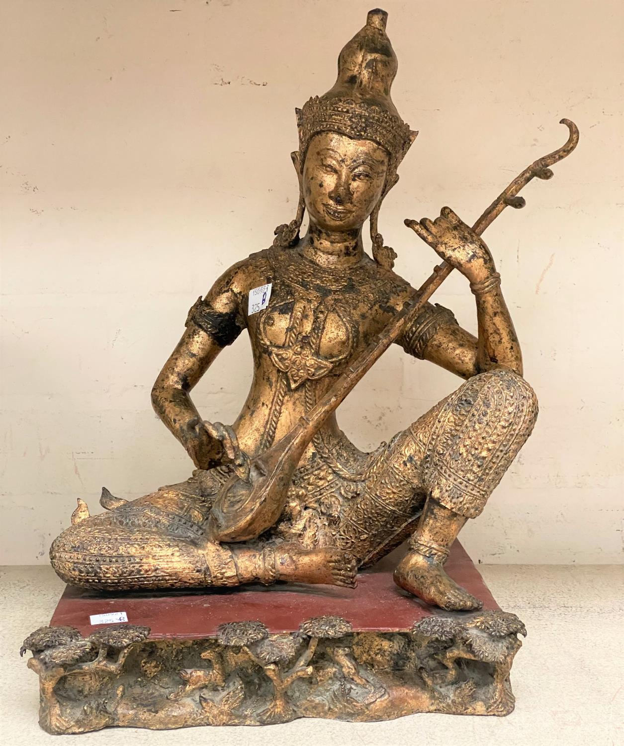 An Asian bronze figure of a seated Buddha playing a musical instrument with gilt highlights and