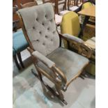 A Victorian stained mahogany rocking armchair with fishtail scroll arms and fawn buttoned upholstery