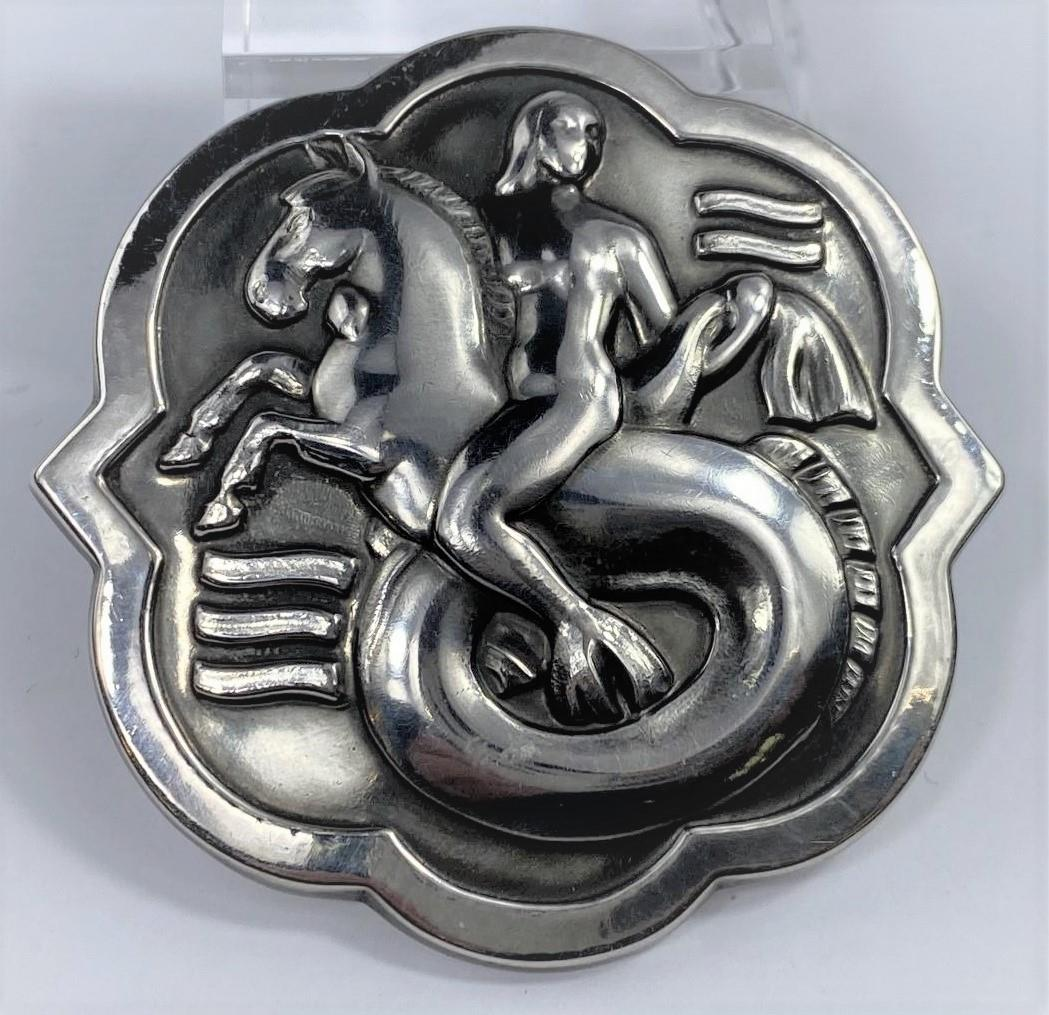 A George Jensen silver brooch designed by Arno Malinowski: mermaid riding on a water horse in waves,