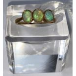 A yellow metal ring set 3 opals, stamped '18ct', 2.6 gm