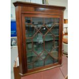 A 19th century mahogany corner cupboard enclosed by single astragal glazed door