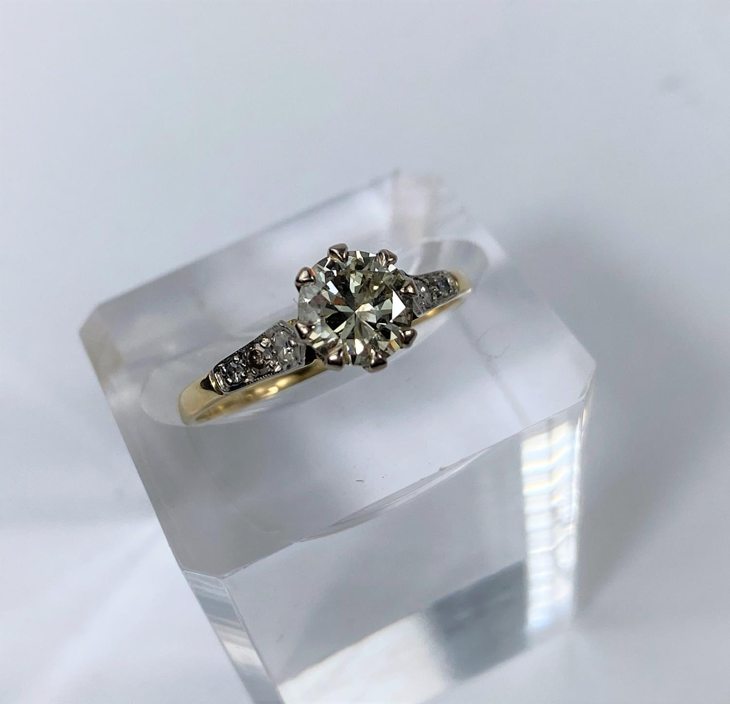 A yellow metal ring set diamond solitaire stone of 1.10 metric carat approx, each shoulder set 3