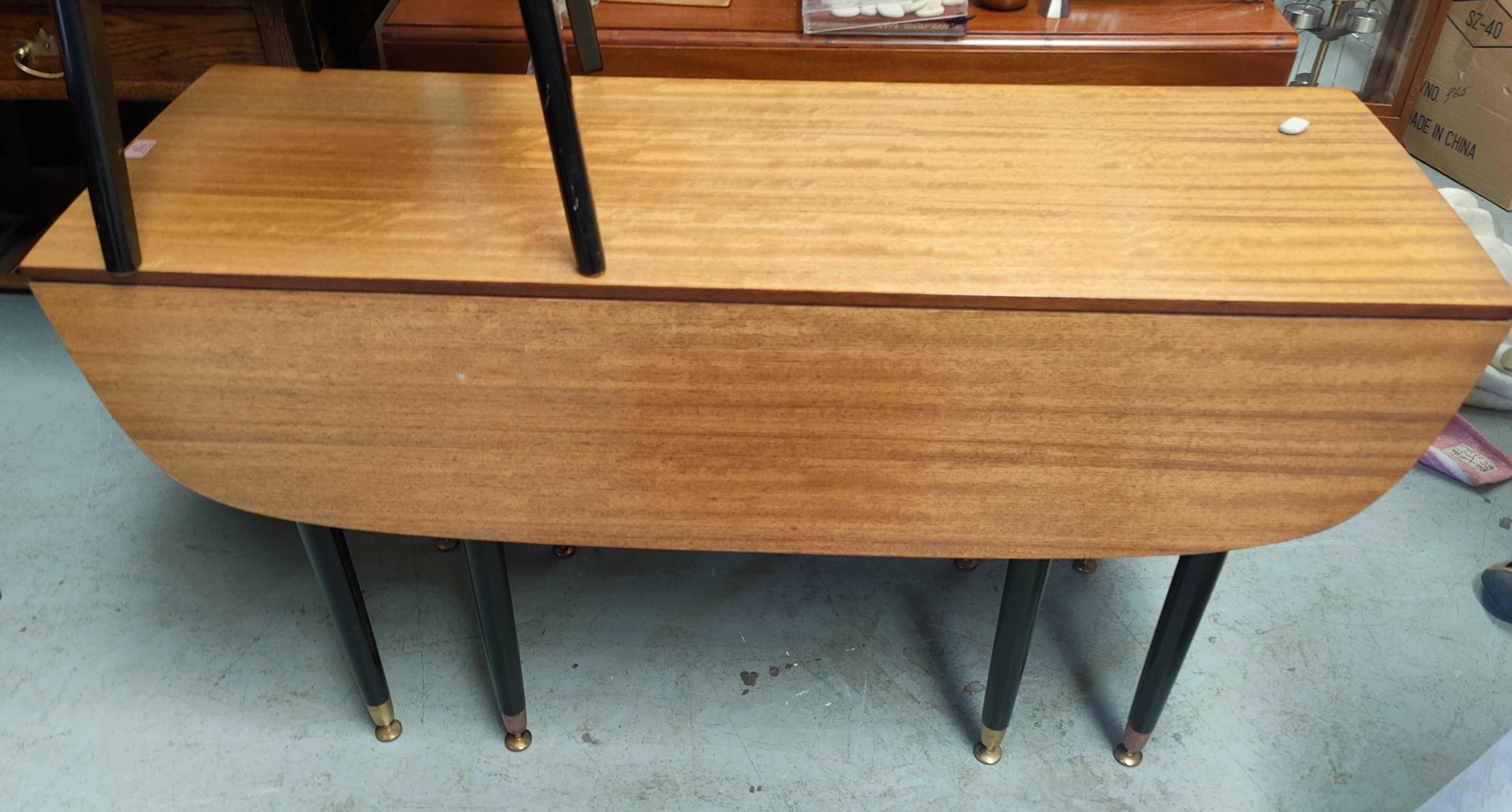 A G-Plan dining suite in ebonised and sapele veneer comprising side cabinet, 122 cm, drop leaf