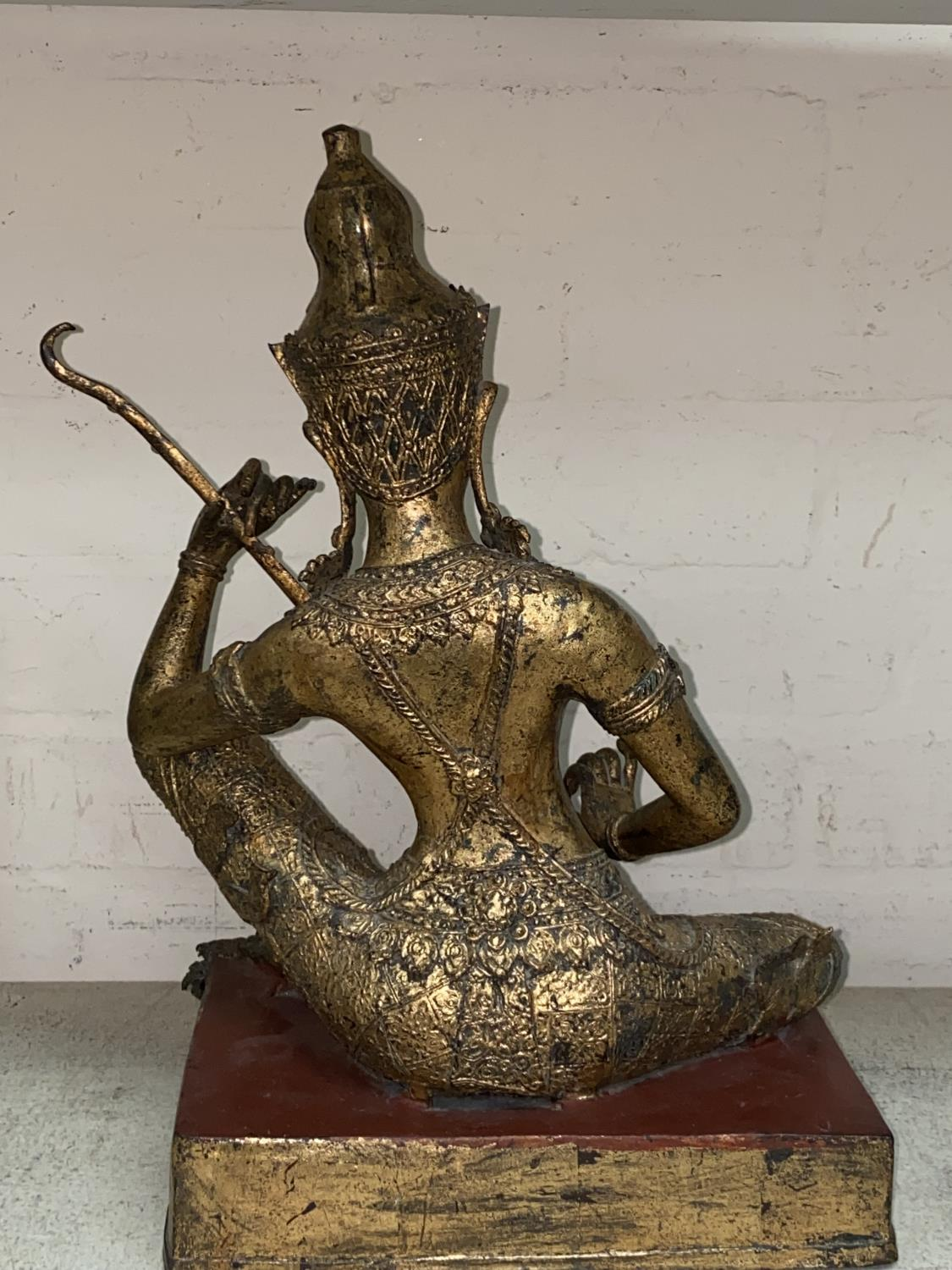 An Asian bronze figure of a seated Buddha playing a musical instrument with gilt highlights and - Image 4 of 4
