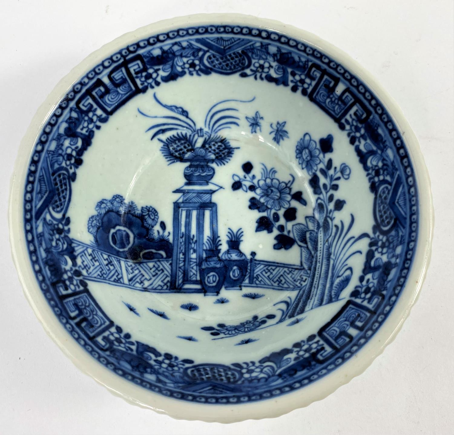 An 18th century Chinese blue and white porcelain bowl with pie crust rim decorated with antiques and