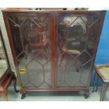 An early 20th century mahogany display cabinet enclosed by 2 astragal glazed doors, on ball and claw