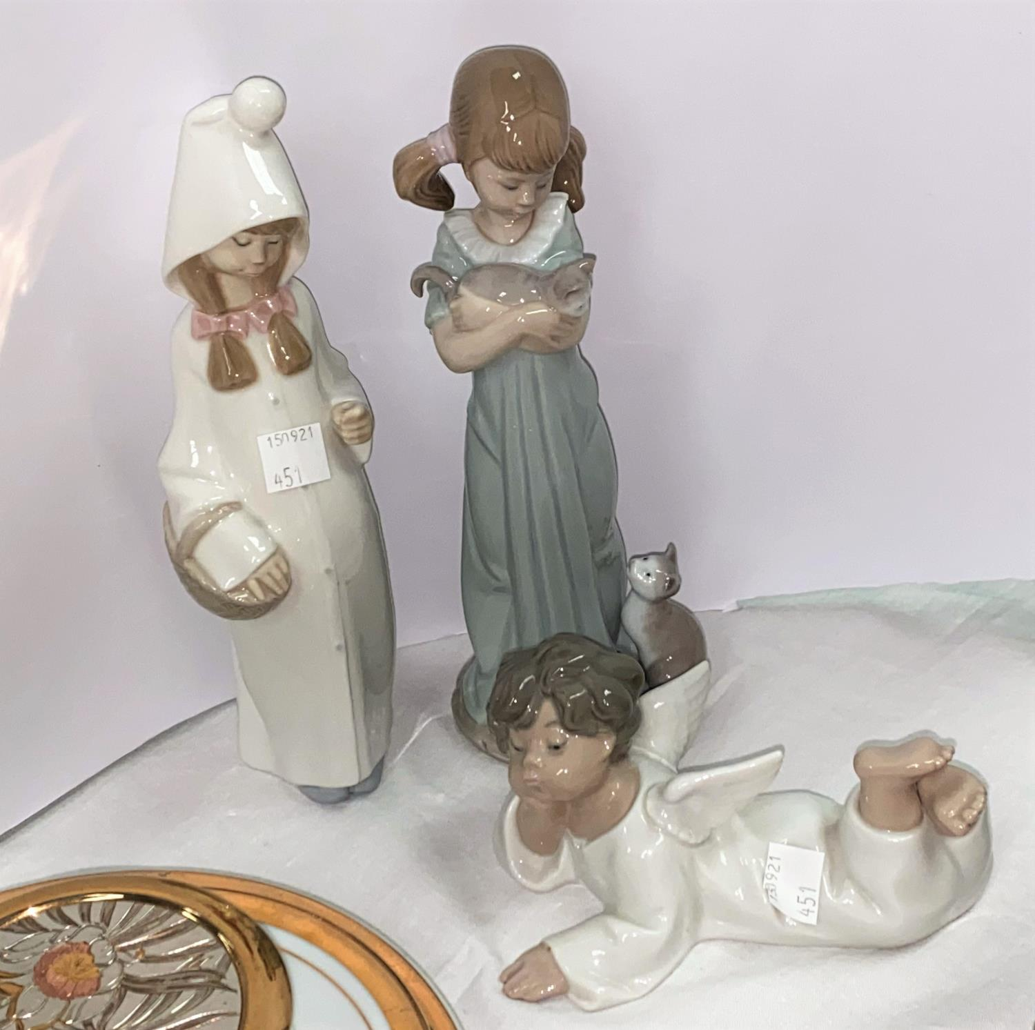 Three Lladro figures: girl with cat, height 29 cm; girl with basket (stick missing); and cherub