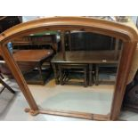An overmantel mirror in pine arch top frame