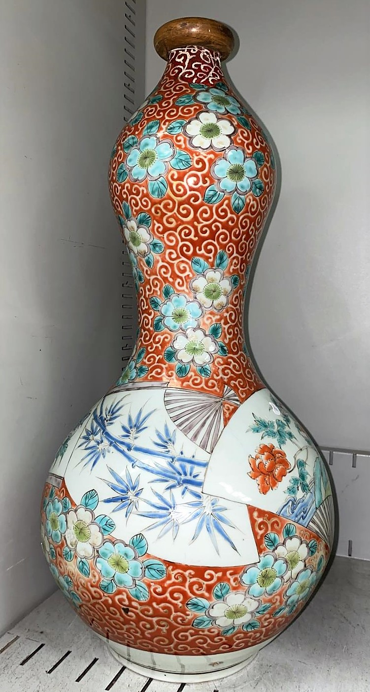 A large Japanese Meiji period double gourd vase with red and gilt decoration of bamboo, fans etc,