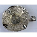 A contiental white metal ashtray, extensively embossed with tavern scenes etc. with side handle,