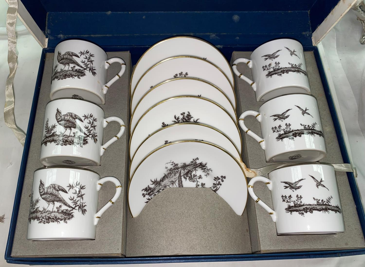 A Royal Worcester black and white coffee service of 12 pieces, boxed; a floral coffee service; cut
