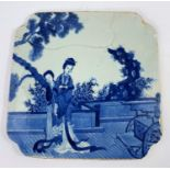 A 19th century Chinese blue and white tile decorated with traditionally dressed female figures, of