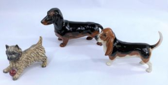 Three Beswick dogs, Dachshund 361, Cairn Terrier with ball 1055A and a Basset Hound 2045.