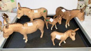 Five Beswick donkeys, three 2267, two foals 2110