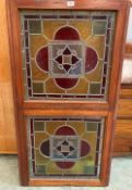 Two Victorian stained glass panels in a pine frame. 50' x 26½'. Cracks, losses