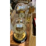 Two anniversary clocks under glass domes