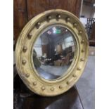 A 19th century convex looking glass, the parcel gilt frame with applied balls to the cavetto. 23'