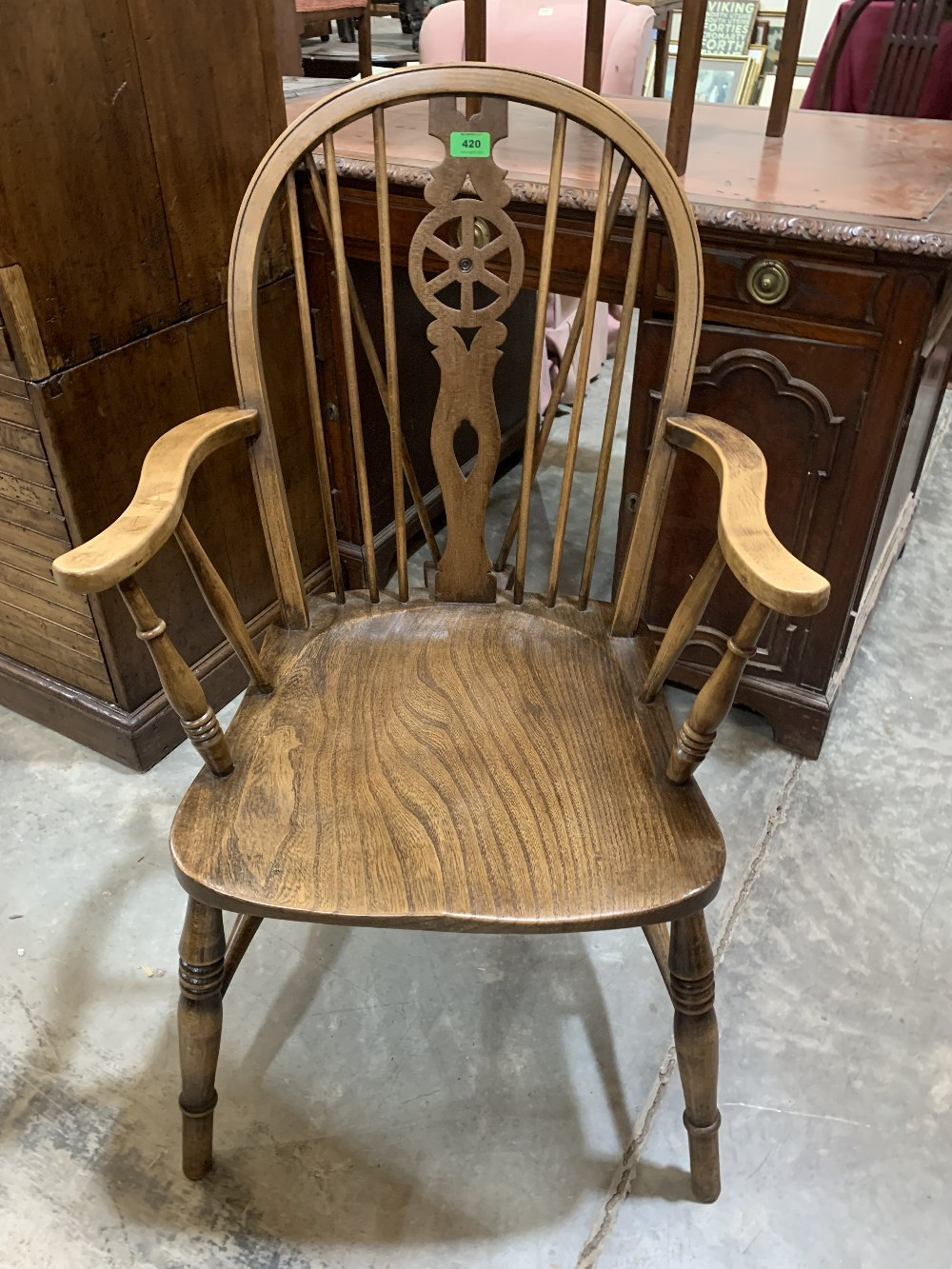 A wheelback elbow chair with elm seat on ring turned splayed legs