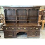 An antique joined oak dresser, the raised rack over three drawers and cupboards flanking an arched