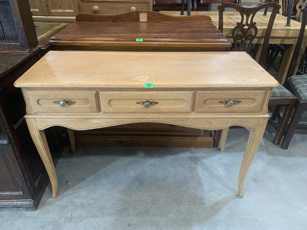 A light oak dressing table with three drawers