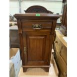 A late Victorian walnut bedside cabinet with frieze drawer