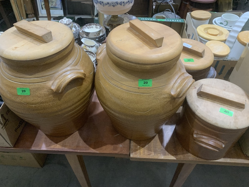 Four earthenware storage jars with beechwood covers, the larger 16½' high.