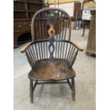 A 19th century Windsor elbow chair on ring turned splayed legs. Reduced in height