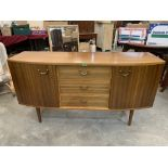 An early 1960s sideboard with a flight of three drawers and cupboards flanking, raised on tapered