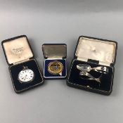 A SILVER POCKET WATCH ALONG WITH A PUSHER SET AND A MEDAL