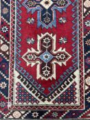 A MIDDLE EASTERN FRINGED AND BORDERED RUNNER AND A RUG