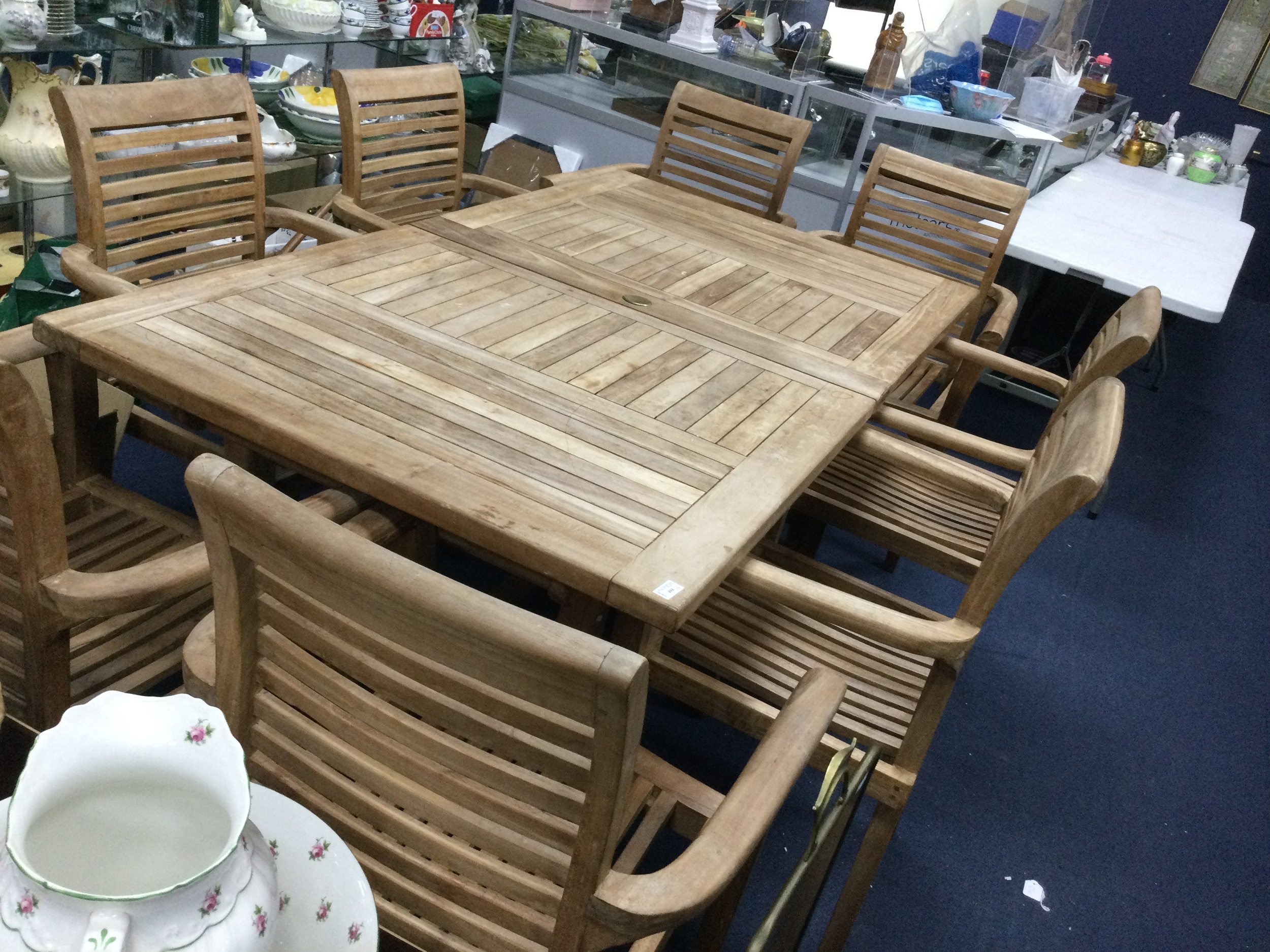 A CONTEMPORARY HARDWOOD EXTENDING GARDEN DINING TABLE AND EIGHT ARMCHAIRS